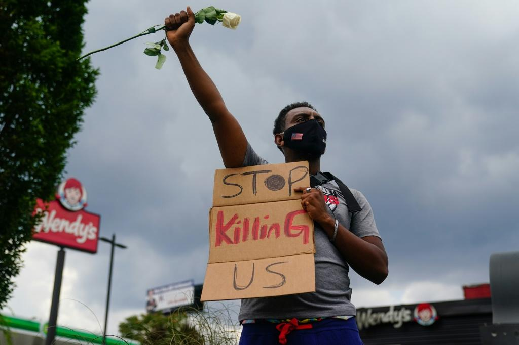 A man holds a sign outside the Wendy's restaurant where Rayshard Brooks was shot dead by police