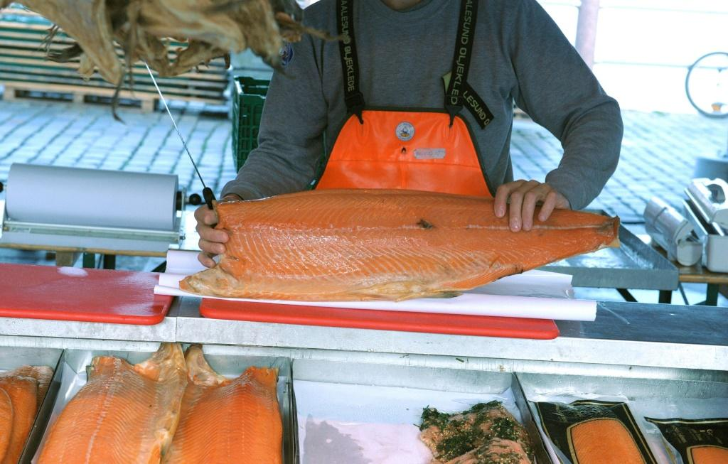A fishmonger cuts salmon at the fish market near the Norwegian harbor of Bergen in September 2014