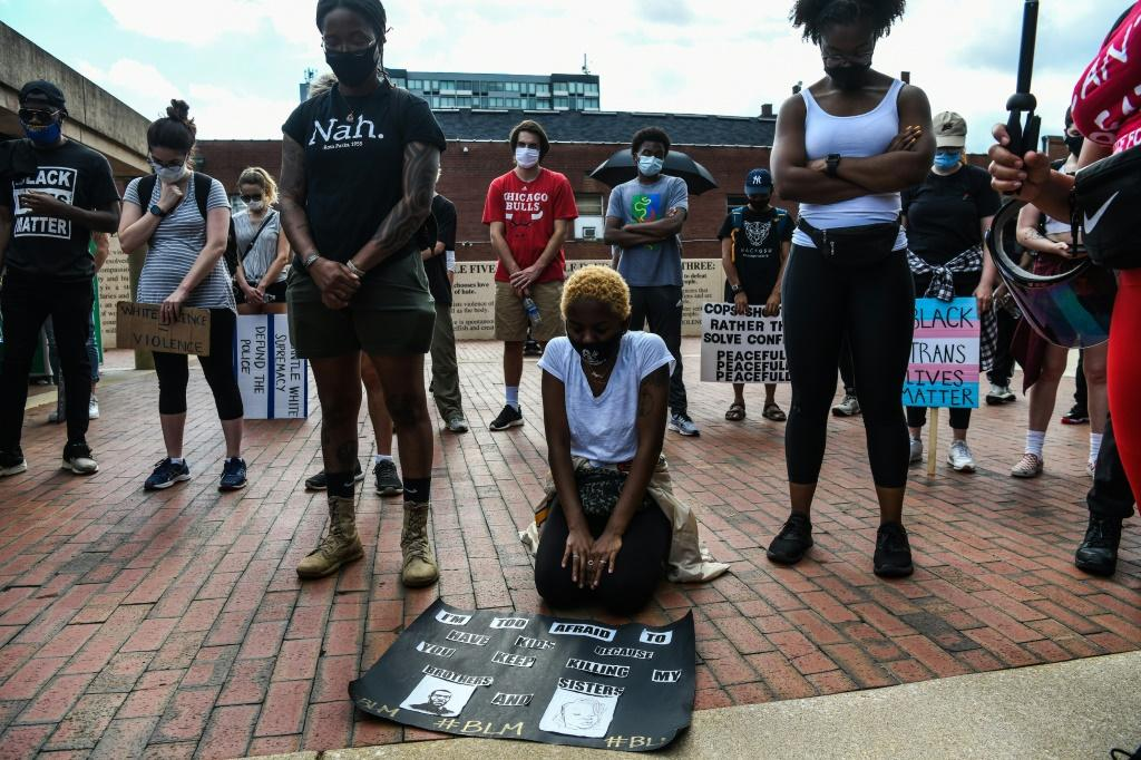 A protester kneels amidst others bowing their heads as they observe eight minutes of silence in honour of Rayshard Brooks at Martin Luther King Jr. National Urban Park n Atlanta