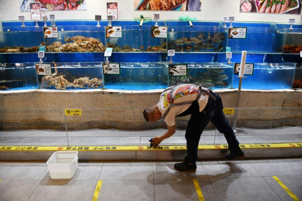 A worker cleans glass in the seafood section of a supermarket in Beijing, where a fresh coronavirus outbreak is keeping customers away