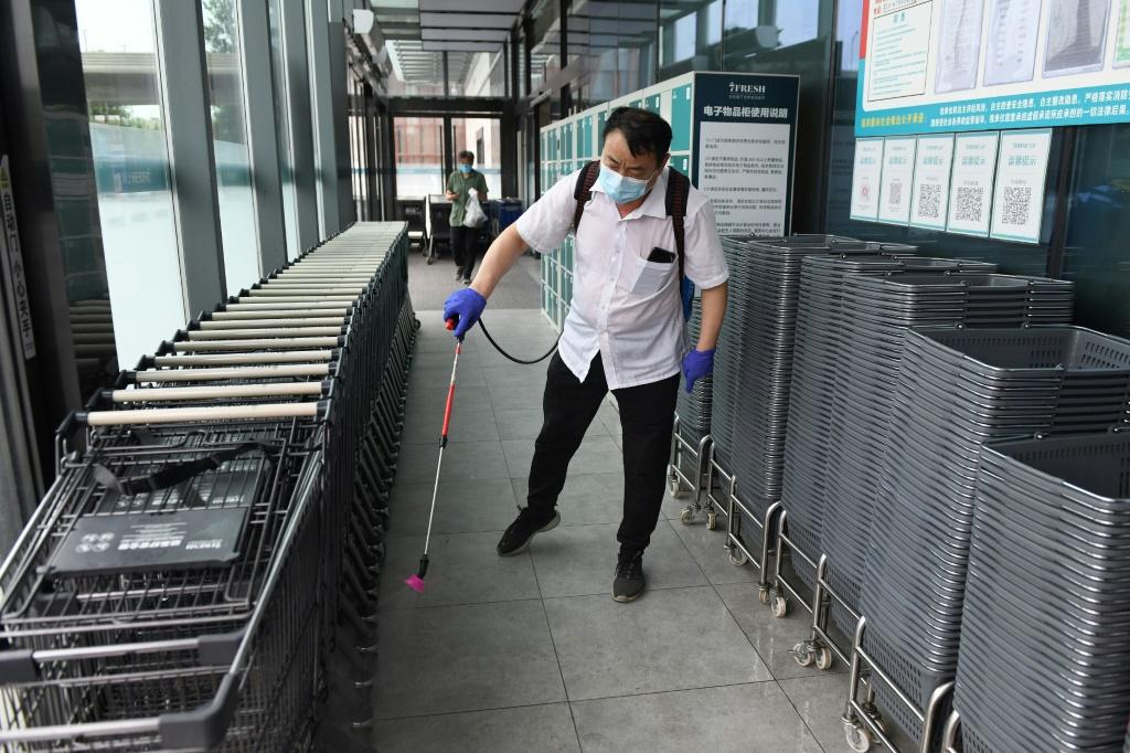 A worker disinfects shopping baskets and carts at the entrance of a supermarket in Beijing