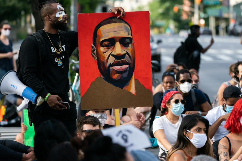 A man holds a picture of George Floyd during a Black Lives Matter protest in New York City