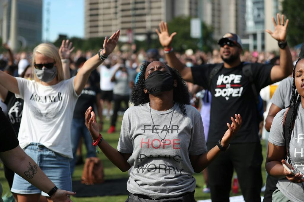 People pray during a Juneteenth event at Centennial Olympic Park in Atlanta, Georgia