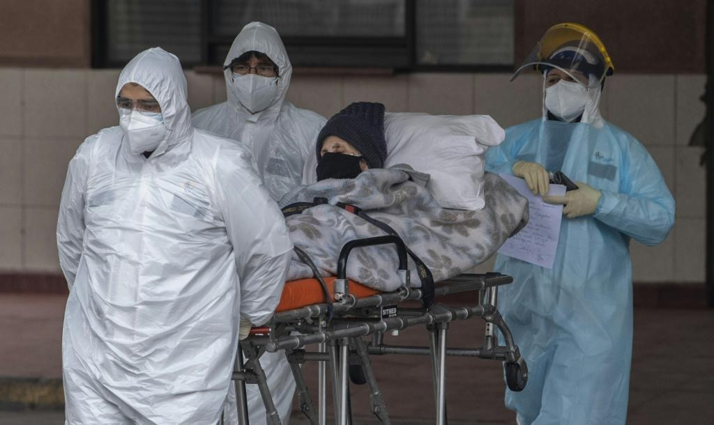 The toll thus increased by 3,069, officials said; pictured are health care staff transferring a patient with symptoms of COVID-19 to San Jose Hospital, in Santiago, on June 18, 2020