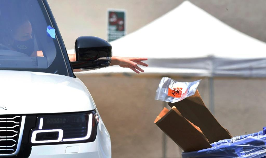 A driver drops off her coronavirus test at a COVID-19 testing site in Los Angeles, California