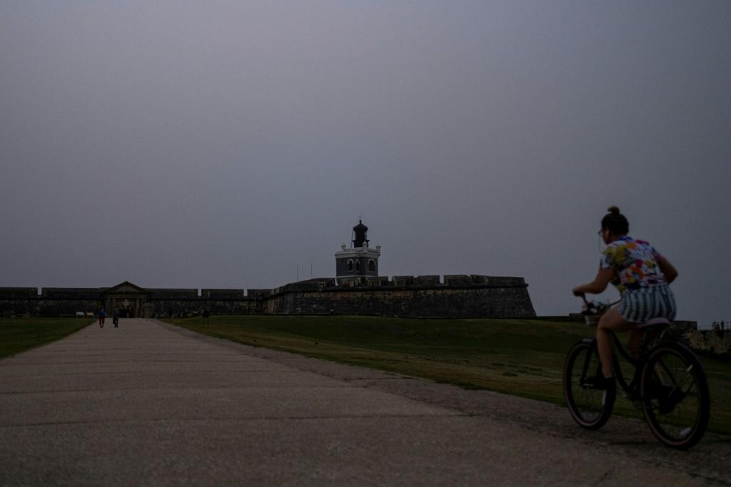 A woman rides her bike in front of El Morro Fort as a vast cloud of Sahara dust blankets the city of San Juan, Puerto Rico on June 22, 2020