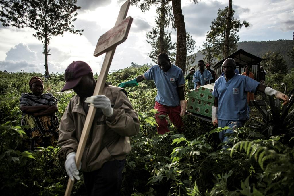 Health workers carry a coffin containing a victim of Ebola in Butembo, eastern DR Congo