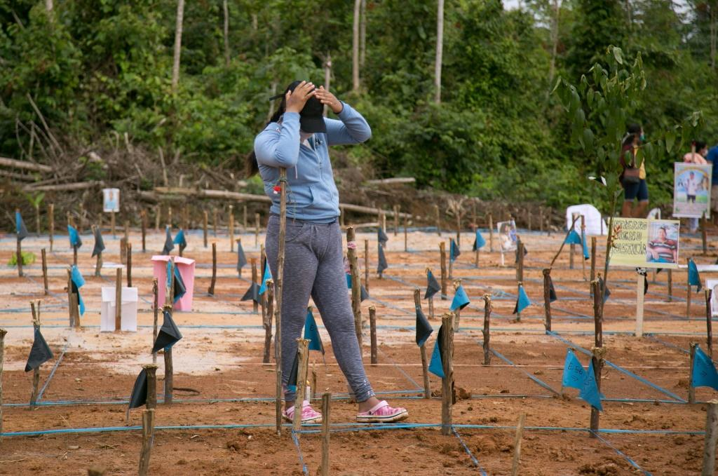 A relative of a victim of COVID-19 gestures as she takes part in a protest at the site of a common grave near Iquitos, Peru, on June 27, 2020