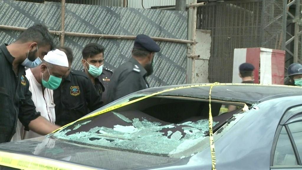 Police examine the scene after four gunmen attacked the Pakistan Stock Exchange in Karachi, where they killed four before being shot dead in a firefight, police said.