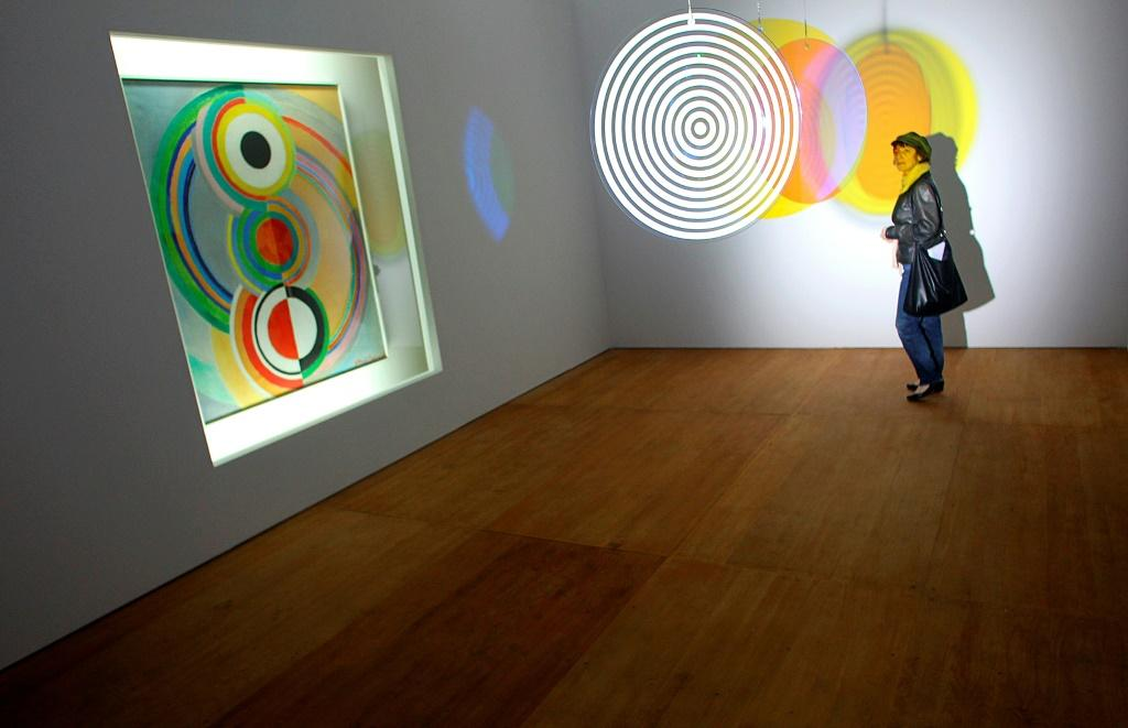 """Painting, """"Rythme"""" (L) by French artist Sonia Delaunay is displayed next to a piece (C) entitled """"Your Concentric Welcome"""" by Olafur Eliasso in Chaumont, eastern France"""