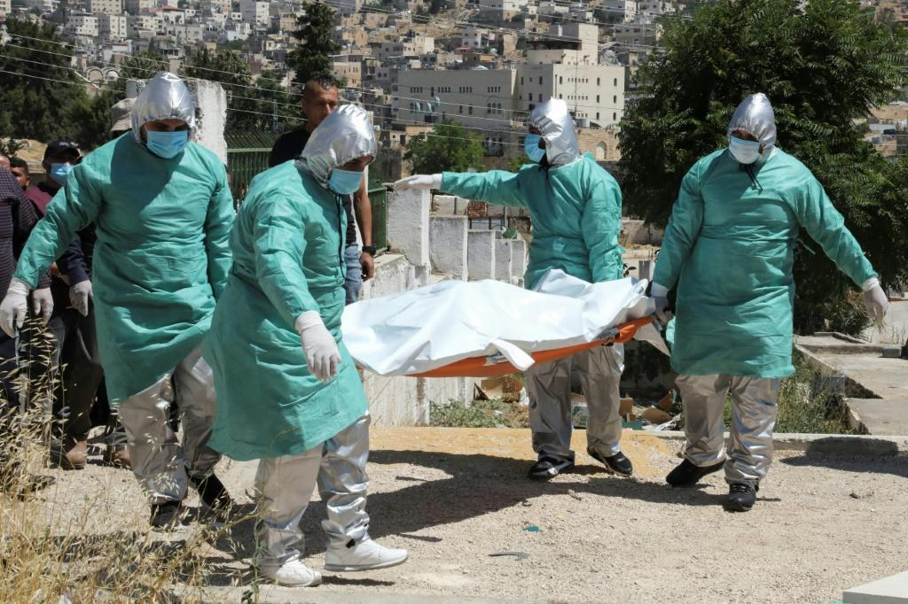Palestinian health workers transport the body of a coronavirus victim for burial