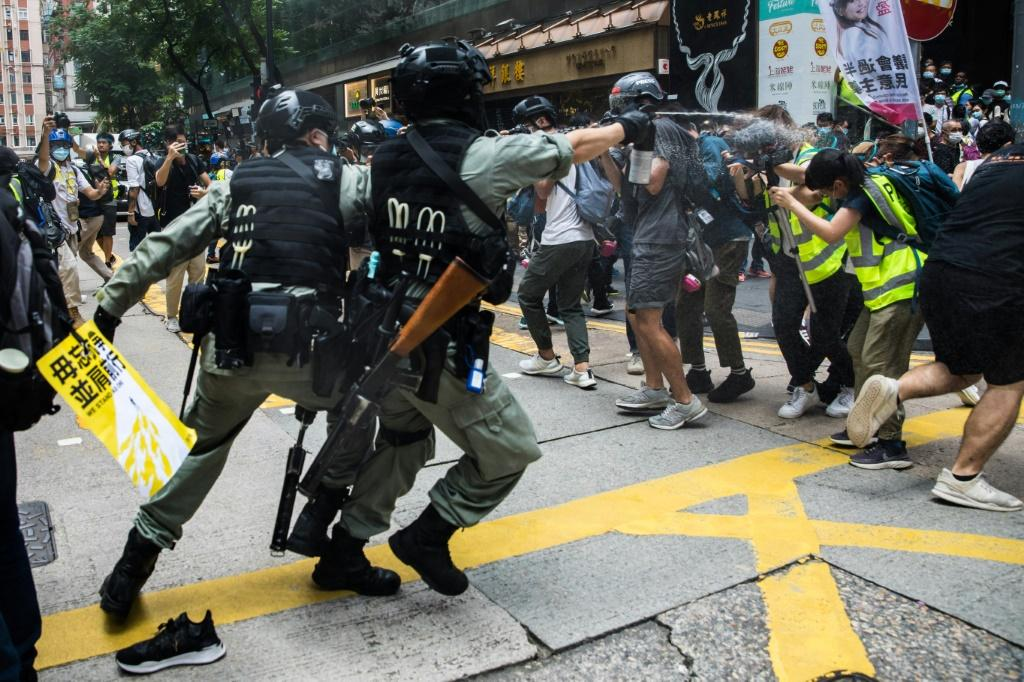 Riot police used pepper spray and made arrests as protesters defied a ban to gather in the popular Causeway Bay shopping district