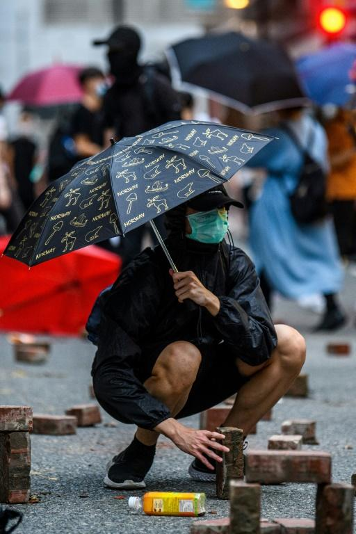 A protester places bricks that were dug up from a nearby sidewalk onto a road during a rally against a new national security law in Hong Kong on July 1, 2020