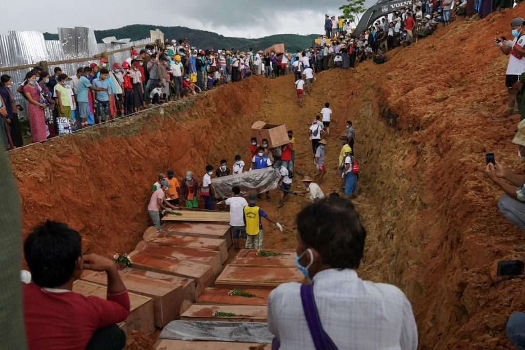 A digger sealed the grave with earth, with many victims yet to be identified