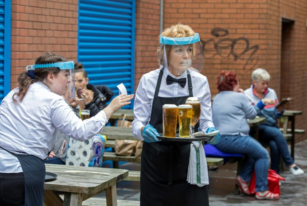 Staff wearing face shields and gloves serve people enjoying a drink in Belfast, Ireland, on July 3, 2020