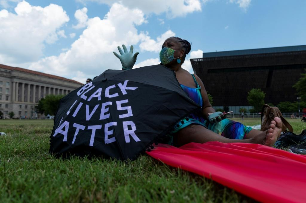 A woman is sitting nearby of her umbrella during a small anti-racism rally near the Washington Monument on July 4, 2020