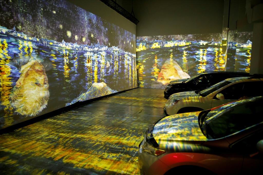 People sit in their cars to experience a drive-in immersive Vincent Van Gogh art exhibit in Toronto, Ontario, Canada on July 3, 2020; amid the coronavirus pandemic, many events are rethinking their programming and innovating for safety's sake
