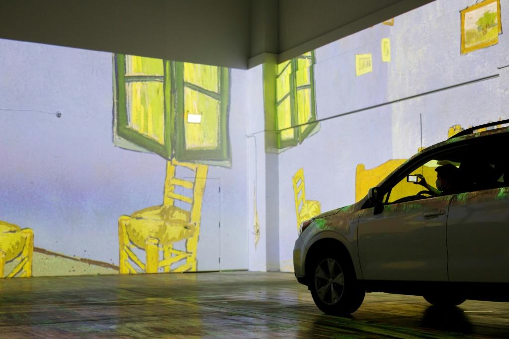 People take photos from their car as they experience a drive-in immersive Vincent Van Gogh art exhibit in Toronto, Ontario, Canada, on July 3, 2020.Amid the coronavirus pandemic, many events are having to rethink their programming and innovate in order to