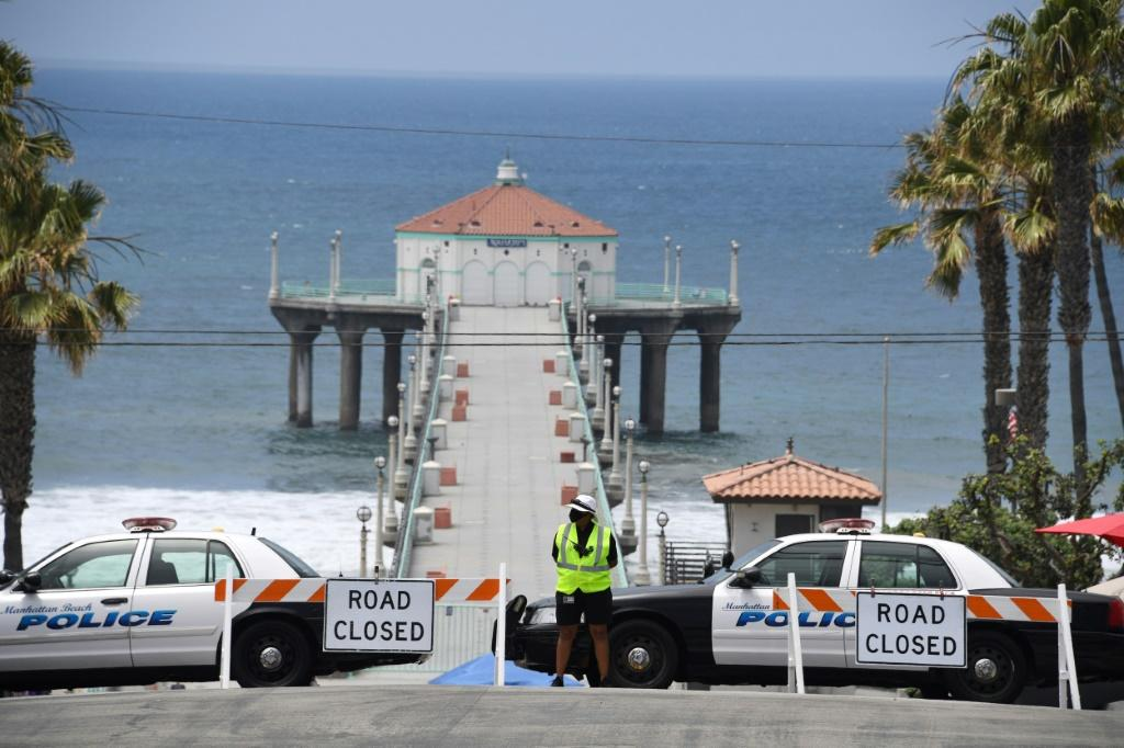 The police block the entrance to the pier Manhattan Beach, California, where beaches are closed due to a spike in COVID-19 cases