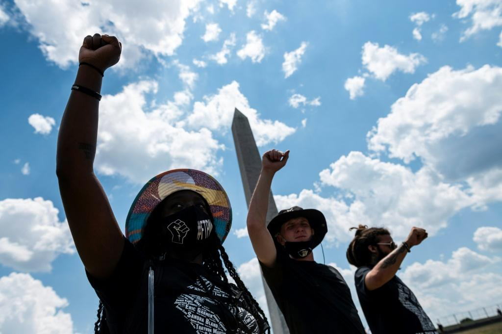 Protests lift fist under one meeting against racism in front of the Washington Monument on July 4, 2020, a national holiday darkened by the coronavirus pandemic, continuing tensions and angry words from President Donald Trump