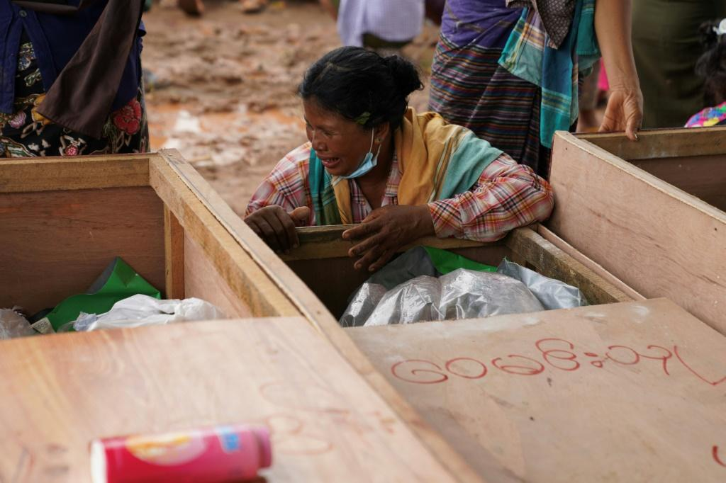 A woman weeps over a body of a jade miner killed in the landslide near Hpakant in Kachin state