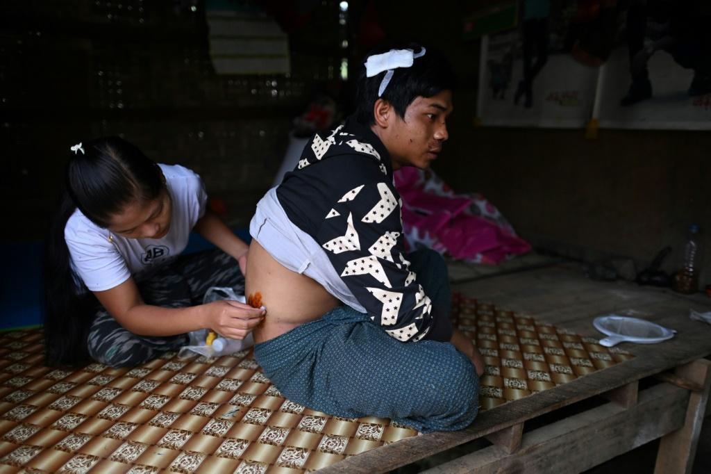 Pan Ei Phyu treats the wounds of husband Sai Ko, who survived the deadly landslide