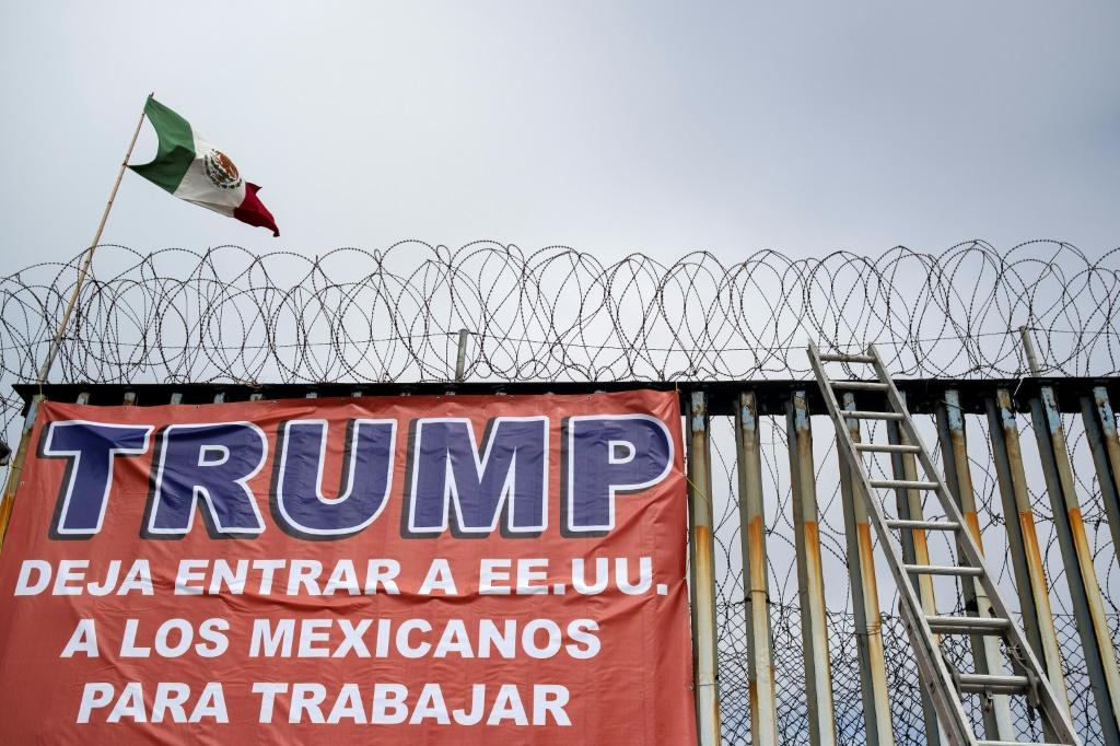A Mexican flag and a banner reading 'Trump, let Mexicans enter the US to work' are seen during a demonstration by members of Border Angels and Alianza Migrante in the Mexican border city of Tijuana in February 2020