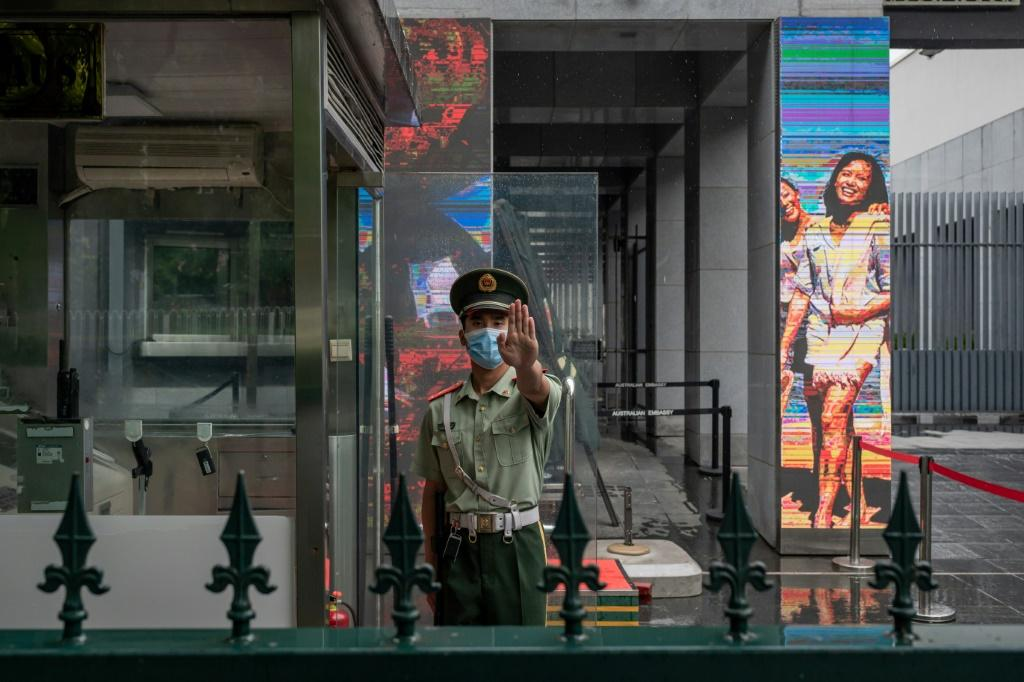 A Chinese paramilitary police officer gestures while standing at the entrance gate of the Australian embassy in Beijing