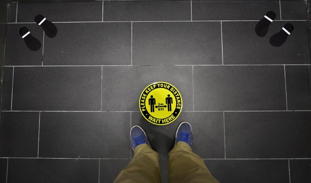 Foot markings and a coronavirus social distance reminder are seen on the floor of an elevator in an office building in Hollywood, California on July 7, 2020