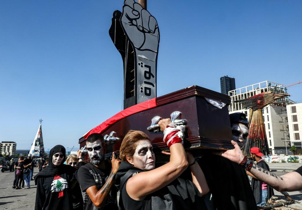Lebanese anti-government protesters take part in a symbolic funeral for the country in the capital Beirut in June