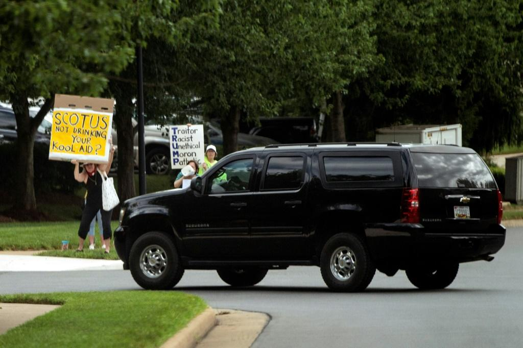 Anti-Trump protesters held up signs as the motorcade carrying President Donald Trump took him to the Trump National Golf Club in Sterling, Virginia on July 11, 2020