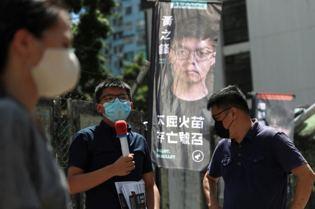 Pro-democracy activist Joshua Wong (C) campaigns for the primary which will choose candidates for upcoming legislative elections