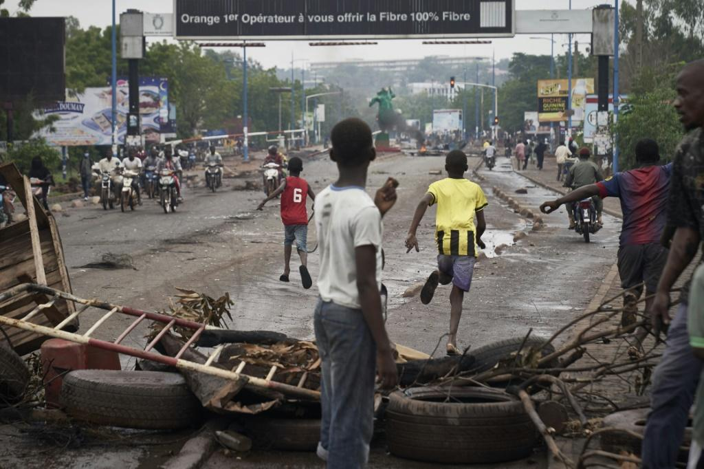 Protesters run from riot police after erecting barricades to block the Martyrs Bridge in Bamako on Saturday