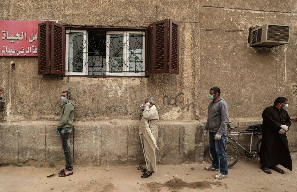 Egyptian men wait outside a centre of non-governmental organisation the Egyptian Food Bank to receive cartons with foodstuffs amid the pandemic on April 5