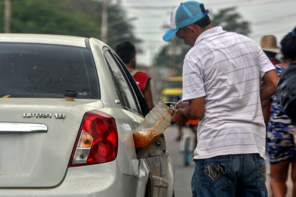 A man fills his car with gasoline purchased on the streets of Maracaibo, Venezuela in July 2020