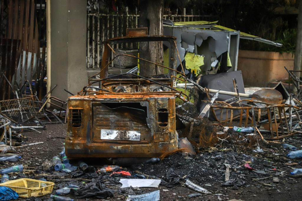 On a main road into town, businesses have been looted and burnt black, their front windows shattered, their walkways covered in twisted scrap metal