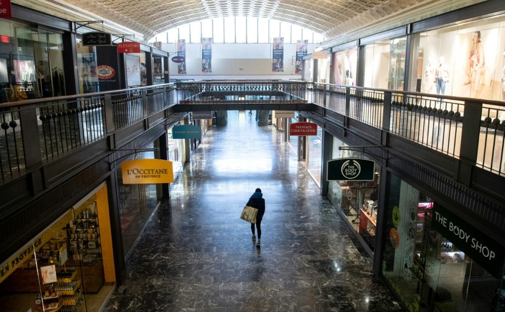 The US economy suffered a 37 percent collapse in GDP in the second quarter -- here, a woman walks through an empty shopping area in Washington in March 2020