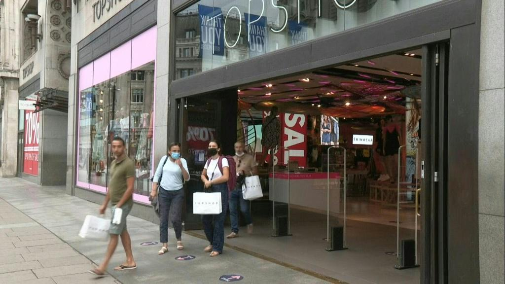 People walk the busy streets of Oxford Street in central London as it becomes compulsory to wear masks in shops