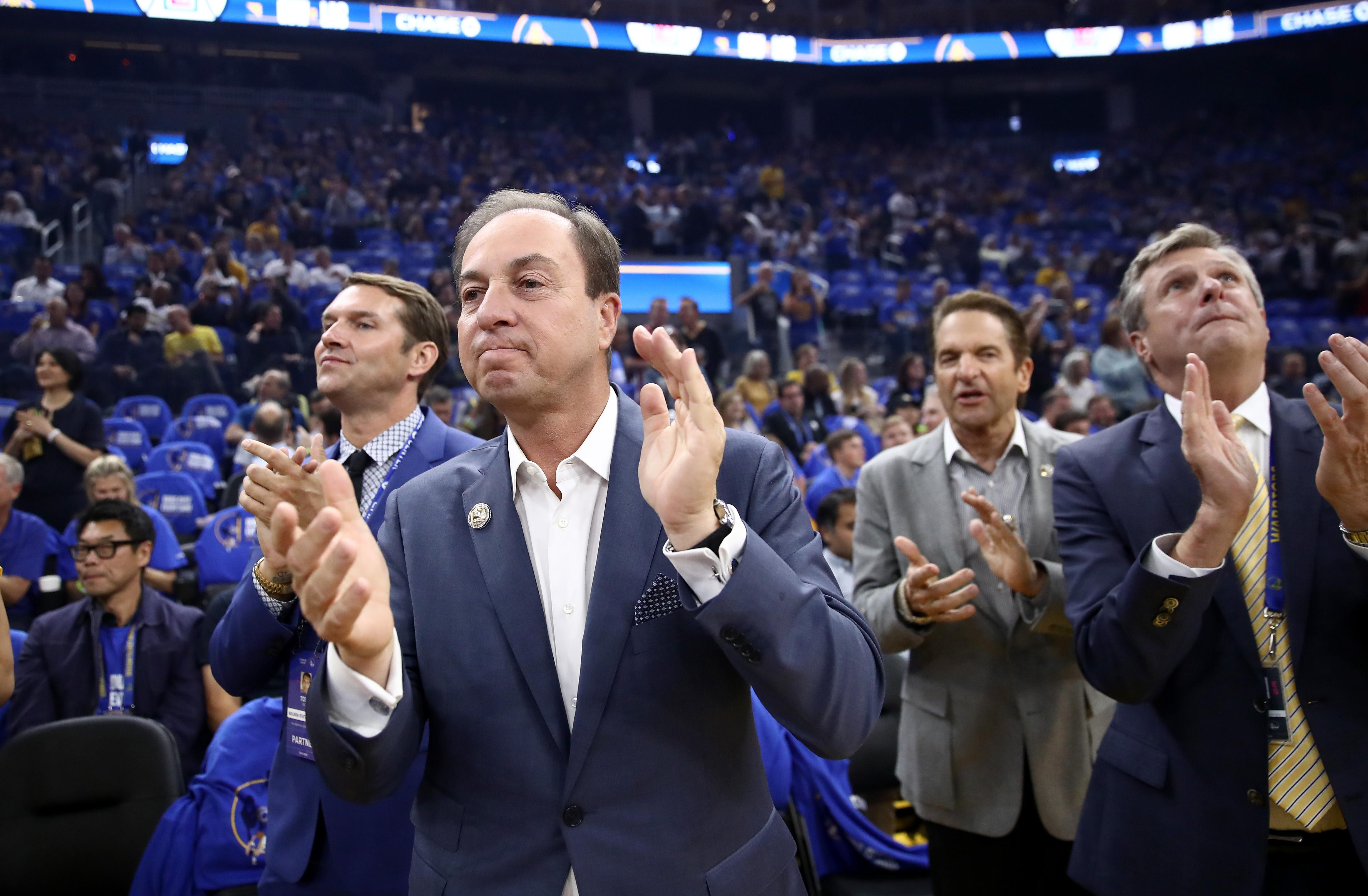 Golden State Warriors owners Joe Lacob and Peter Guber stand with team president and COO Rick Welts