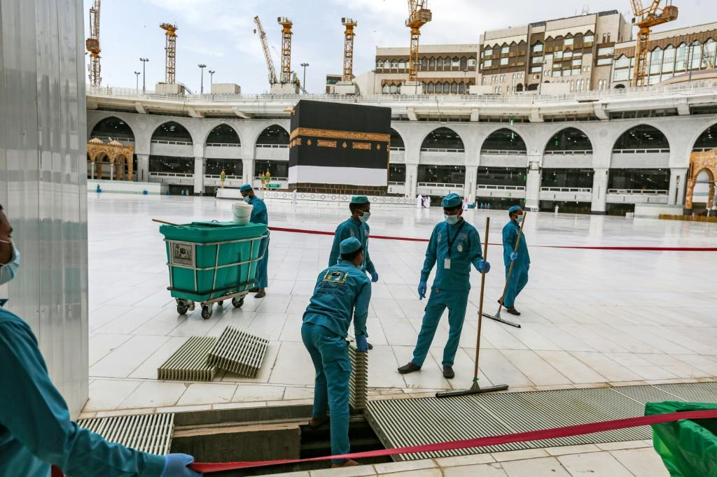 Workers clean the area around the Kaaba, the structure at the centre of the Grand Mosque towards which Muslims around the world pray