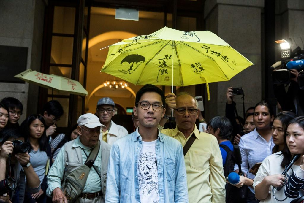 Hong Kong police are seeking to arrest Nathan Law (C) and five other democracy activists now living in exile, China's state television reported