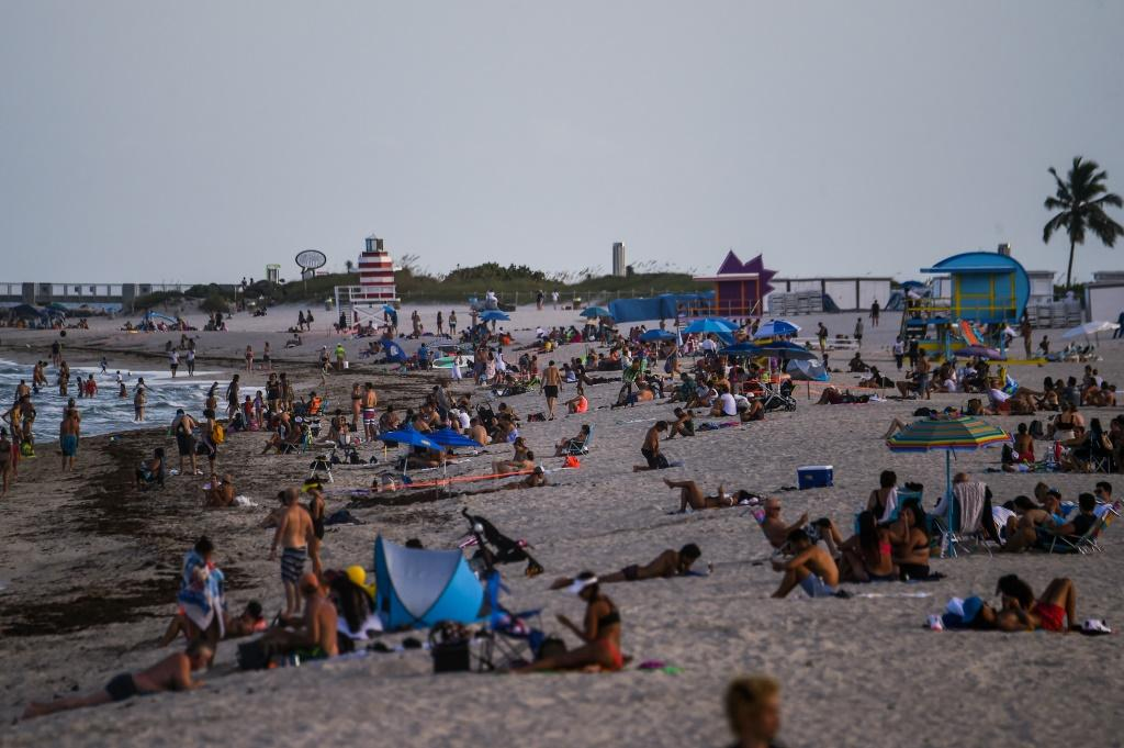 People relax on the beach in Miami Beach, Florida -- a state seeing record numbers of COVID-19 deaths