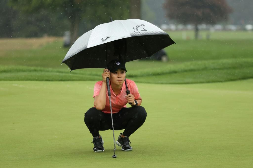American Danielle Kang lines up a putt under an umbrella Saturday on her way to a one-over par 73 that kept her in a share of the lead at the LPGA Drive On Championship at Inverness Club in Toledo, Ohio