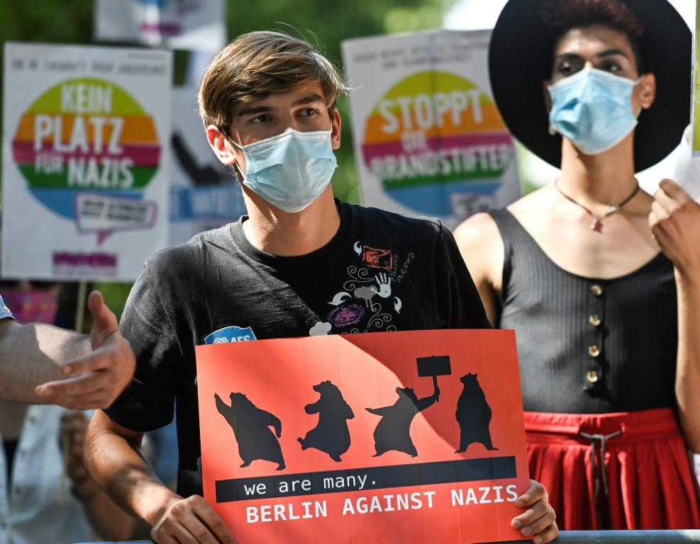 """As politicians slammed the rally, a small number of counter-protesters gathered, one holding a sign reading """"we are many. Berlin against Nazis"""