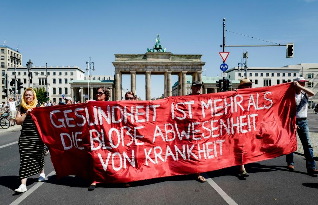 """Marchers unveil a banner reading """"health is more than the simple absence of illness"""