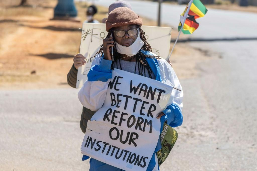 Zimbabwean novelist Tsitsi Dangarembga holds a placard during an anti-corruption march along Borrowdale road, in Harare; she was arrested and freed on bail the following day