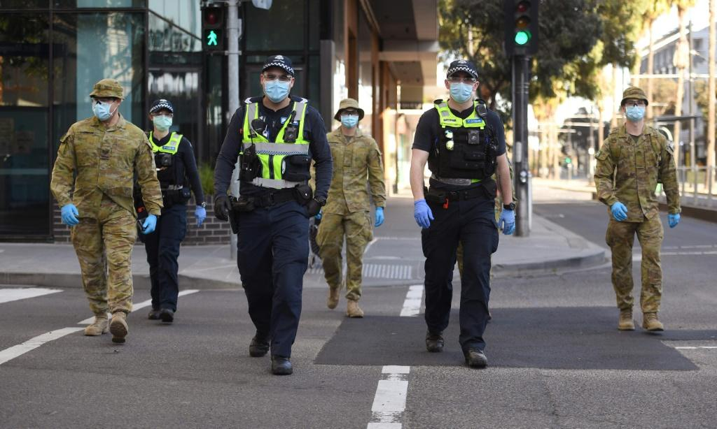 A group of police and soldiers patrol the Docklands area of Melbourne after the announcement of new restrictions to curb the spread of the coronavirus