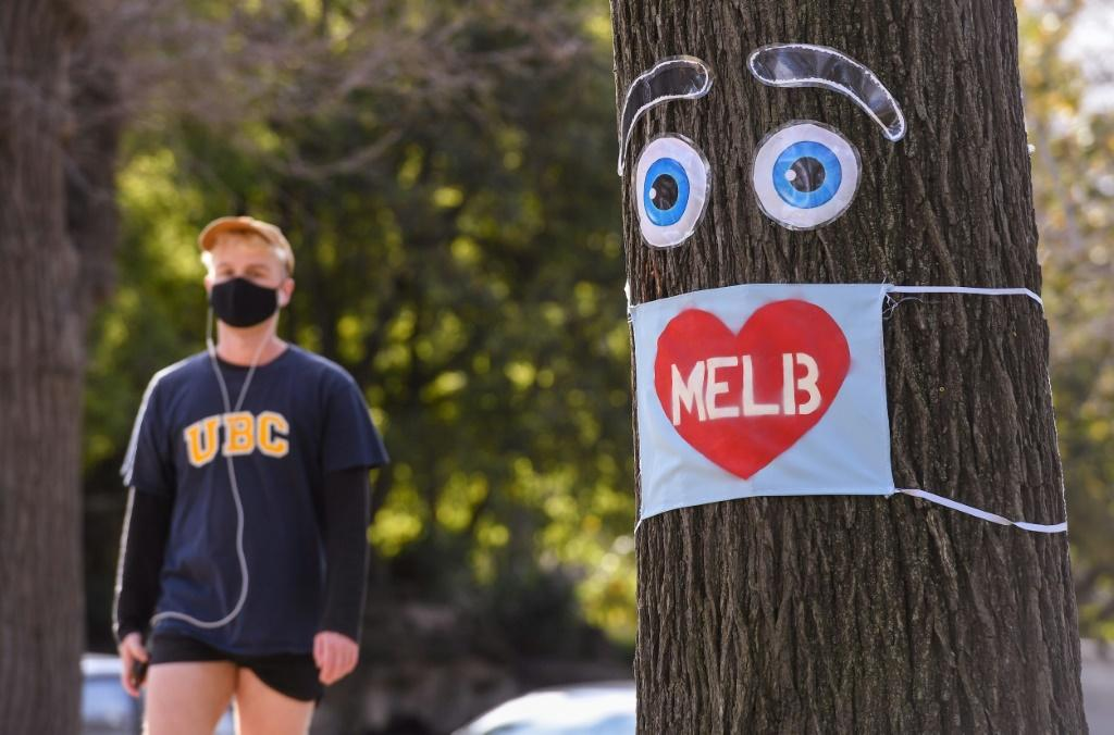 A man walks past a large face mask pinned to a tree in Melbourne after the state announced new restrictions to stop the spread of COVID-19