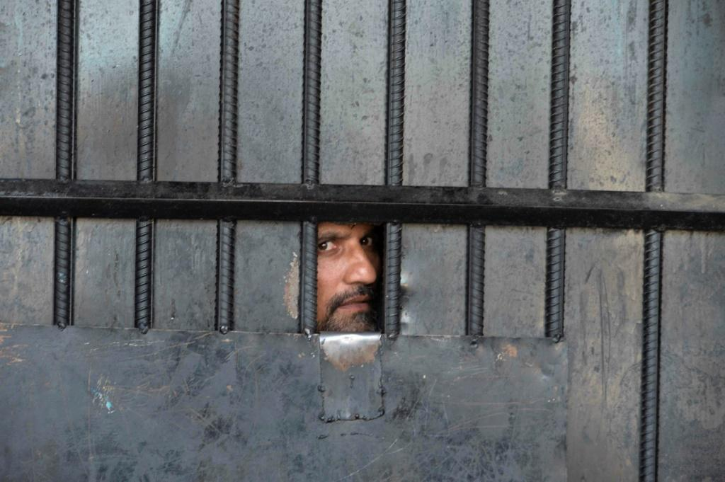 A man watches from behind a closed gate after a raid at the prison in Jalalabad