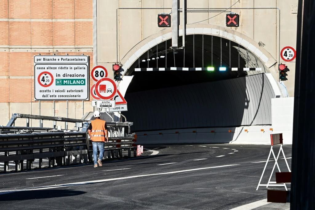A worker walks near a tunnel before the opening of the new San Giorgio bridge for vehicles